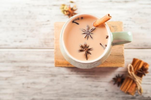 A cup of masala tea. spices cloves, fennel, cinnamon, cardamom, milk.