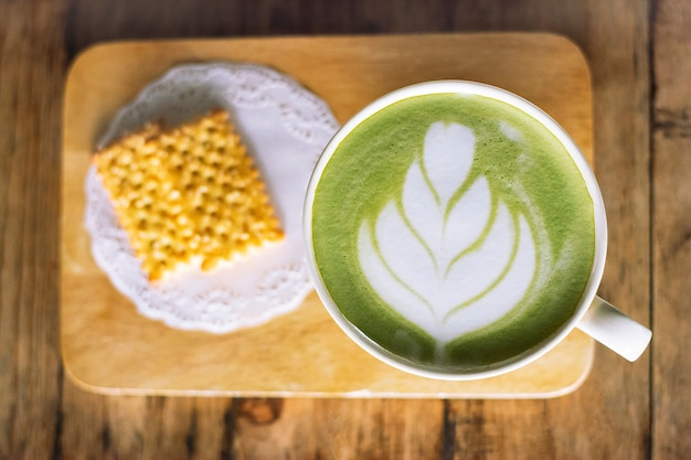 Cup of matcha latte green tea on dark wooden background.