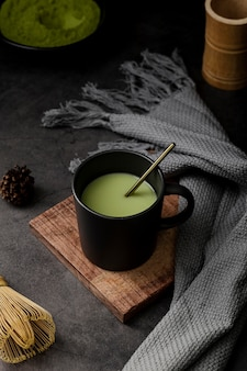 Cup of matcha tea with textile and pine cone