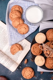 Cup of milk and book with biscuits