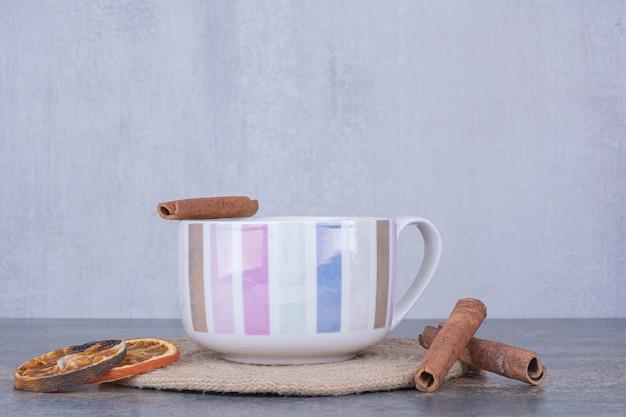 Tazza di caffè al latte con bastoncini di cannella e fette d'arancia. foto di alta qualità
