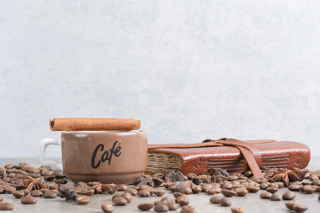 Cup of milk coffee with coffee beans and notebook. high quality photo