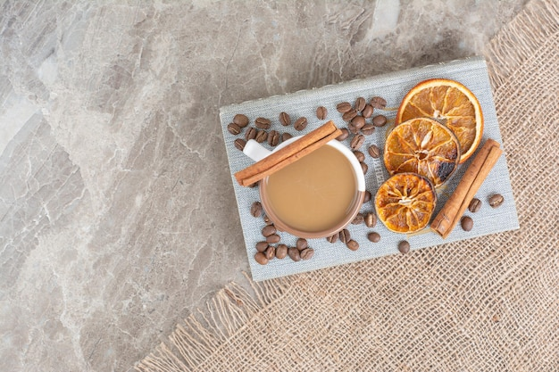 Tazza di caffè al latte con chicchi di caffè e fette d'arancia sul libro. foto di alta qualità
