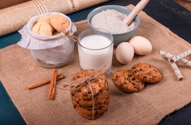 Cup of milk and flour with jar of biscuits and egg