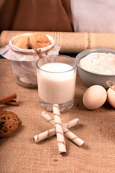 Cup of milk and flour with jar of biscuits
