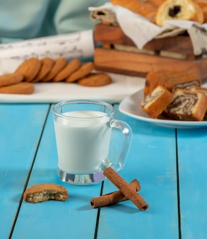 A cup of milk with cinnamon sticks and a cookie.