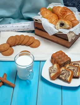 A cup of milk with cinnamon sticks and pastries on the table.