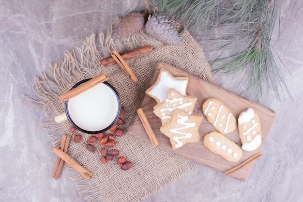 Una tazza di latte con pan di zenzero stellati e cannella intorno