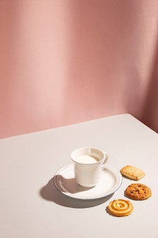 Cup of milk with variety of cookie on table