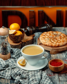 A cup of milky coffee with lemon slices and dough pie around.