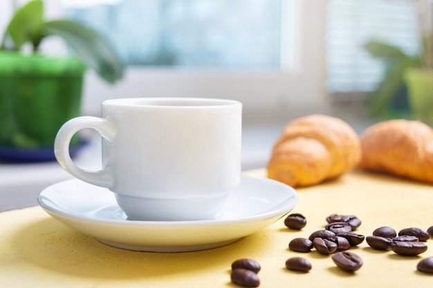 A cup of morning coffee on the table in front of the window and fresh croissants for breakfast.