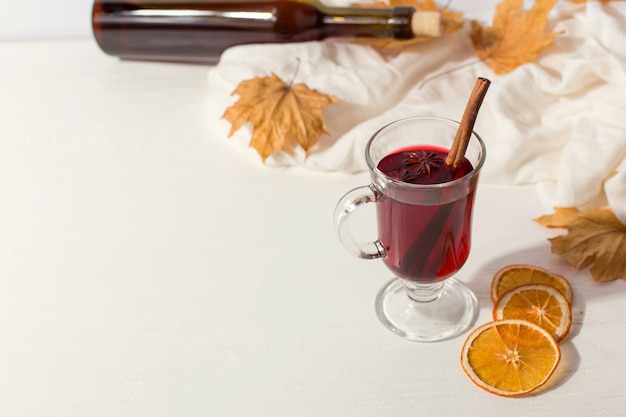 A cup of mulled wine with spices, bottle, a scarf, dry leaves and oranges on the table. autumn mood, a method to keep warm in the cold, copyspace.