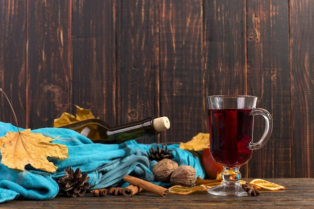 Cup of mulled wine with spices, bottle, scarf, dry leaves and oranges on a wooden table. autumn mood, method to keep warm in the cold, copyspace.