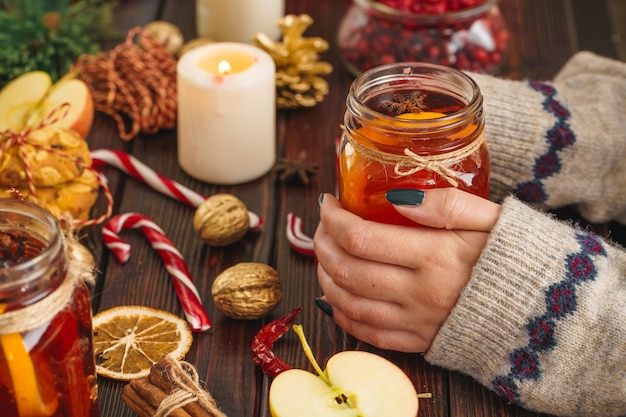 Cup of mulled wine in womans hands on wooden table