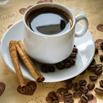 A cup of natural coffee beans and cinnamon