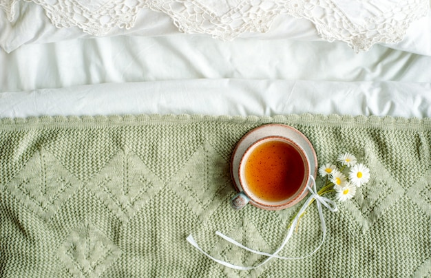 Cup of natural herbal tea from mint and lemon balm in bed,morning close up. cozy atmosphere.openwork lace,cotton white blanket,summer daisy flowers.breakfast.provence and retro style.