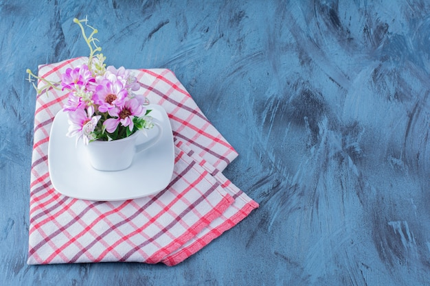 Cup of natural purple flowers with leaves on blue.