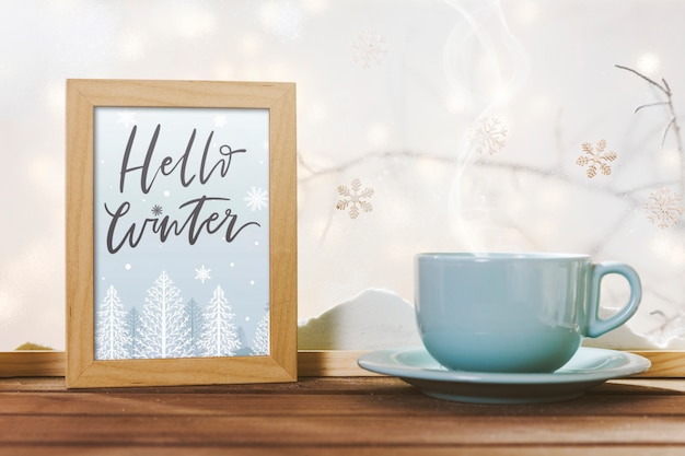 Cup near frame with hello winter title on wood table near bank of snow