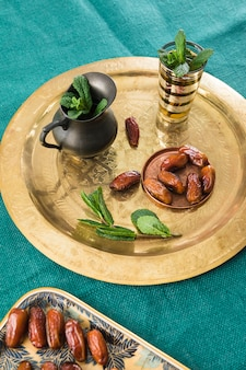Cup near pitcher with plant and dried fruits on tray