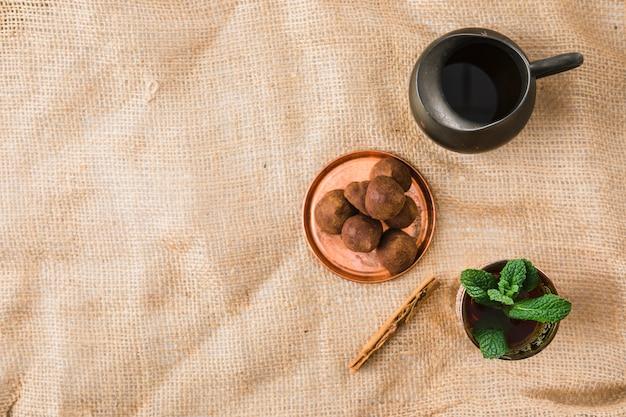 Чашка возле ретро кувшин и сладости на морщинистой мешковины