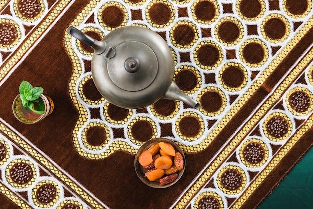 Чашка рядом с ретро чайником и сухофруктами на коврике