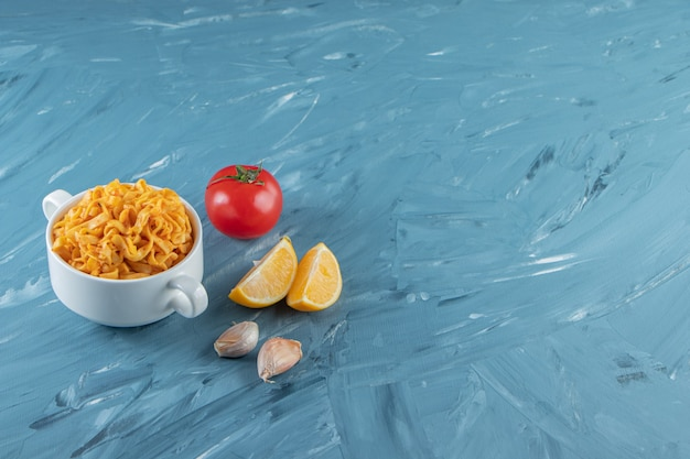 A cup of noodle next to vegetables, on the marble background.