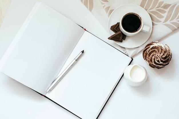 Чашка черного кофе с конфетами и кексами и открытый блокнот на белом фоне