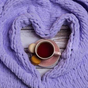 하트 모양의 격자 무늬가 있는 마카롱을 넣은 차 한잔. 아늑한 휴일의 개념입니다.