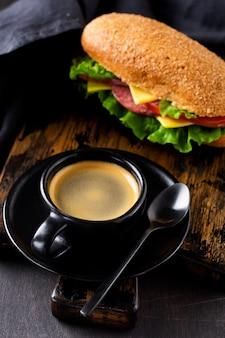素朴な木製のスタンドに、香り豊かなコーヒーと、ふすまパン、チーズ、レタス、トマト、スライスしたサラミ、絞りたてのオレンジジュースを添えたヘルシーなサンドイッチ。朝食のコンセプト。上面図