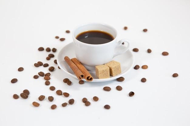 シナモンとコーヒー豆と香りのよいコーヒーのカップ
