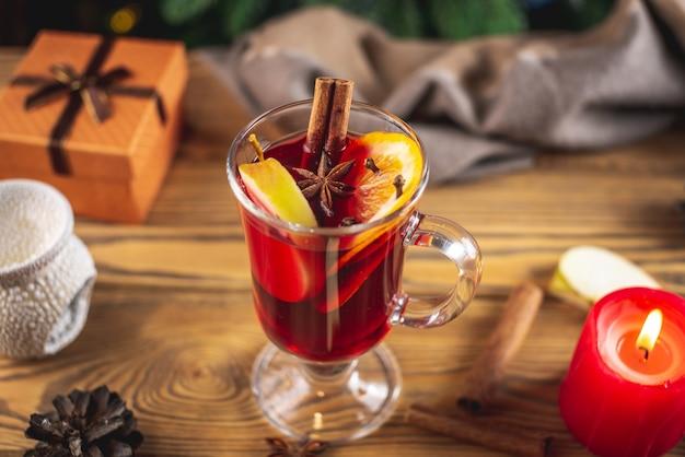 Чашка ароматного горячего глинтвейна на деревянном столе