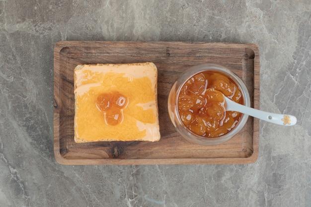 Чашка ягодного варенья с ложкой и тостами на деревянной тарелке. фото высокого качества