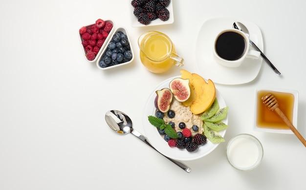 Чашка черного кофе, тарелка овсянки и фруктов, мед и стакан молока на белом столе, здоровый утренний завтрак, вид сверху