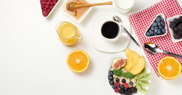 Чашка черного кофе, тарелка овсянки и фруктов, мед и стакан молока на белом столе, здоровый утренний завтрак