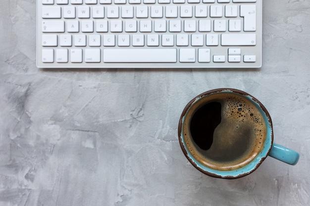 회색 소박한 배경에 검은 커피와 컴퓨터 키보드의 컵. 평평하다, 평면도, 복사 공간, 소셜 미디어 템플릿, 아침 및 인터넷 개념