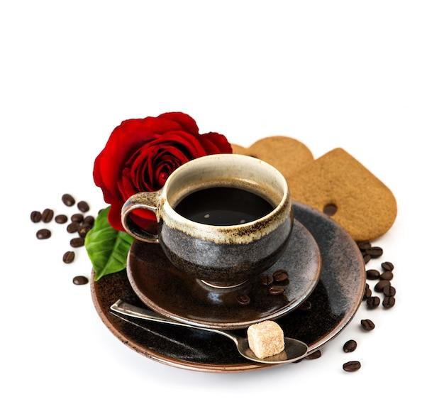 ブラックコーヒーと白い背景の上の赤いバラの花のカップ。お祭りのアレンジ。セレクティブフォーカス