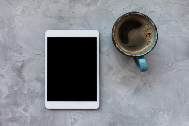 블랙 커피와 회색 소박한 배경에 태블릿 컵. 평평하다, 평면도, 복사 공간, 소셜 미디어 템플릿, 아침 및 인터넷 개념