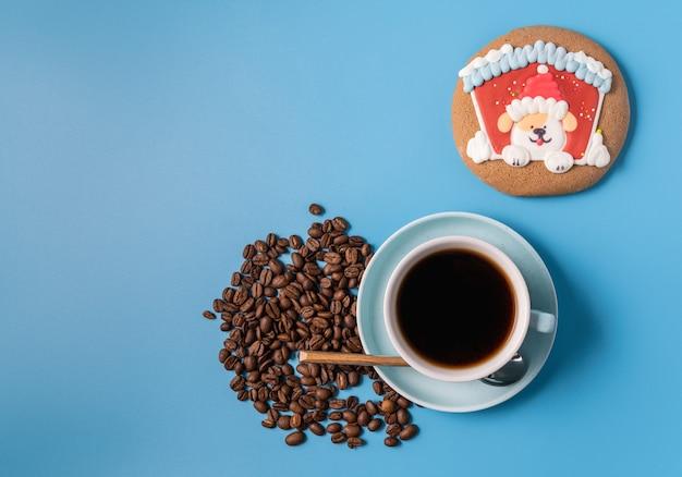 黒のコーヒー、コーヒー豆、青の背景にジンジャーブレッドのカップ、テキスト用のコピースペース。クリスマスのコンセプト。
