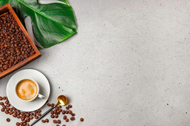 Чашка черного кофе, кофейные зерна в деревянной коробке и лист монстера на сером бетонном фоне, вид сверху