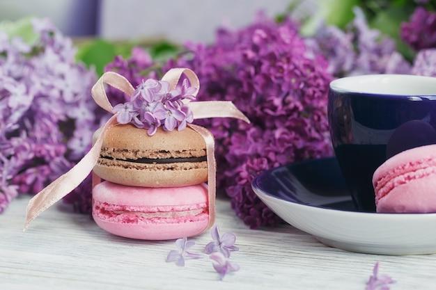 明るい木製のテーブルにブラックコーヒー、ライラックの花、甘いパステルフレンチマカロンのカップ