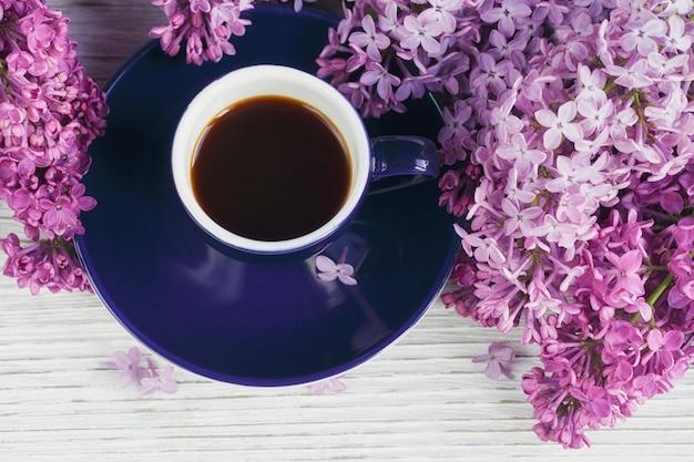 ブラックコーヒーのカップ、明るい木製のテーブルにライラックの花