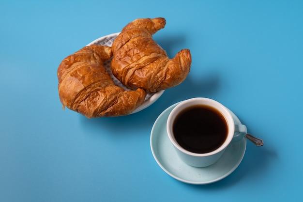 クロワッサン、テキスト用のコピースペースと青い背景の上のブラックコーヒーのカップ。