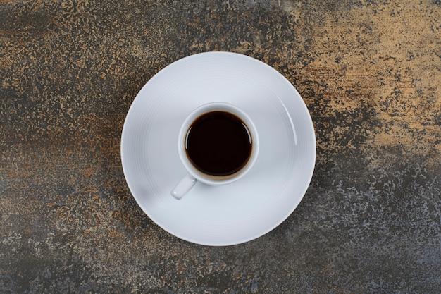 Чашка черного кофе на мраморной поверхности.