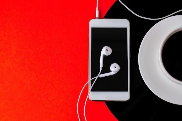 ビニールの記録にあるブラックコーヒーのカップ。スペースをコピーします。音楽を聴く。レトロなスタイル。ポッドキャスト。ヘッドホン付き携帯電話。