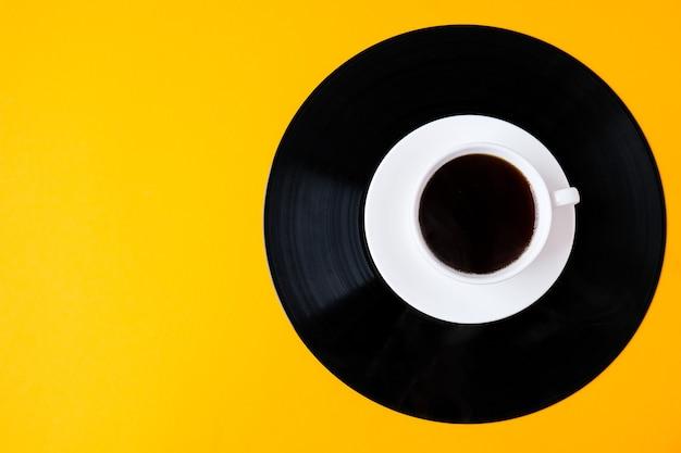 ビニールの記録にあるブラックコーヒーのカップ。スペースをコピーします。音楽を聴く。レトロなスタイル。ポッドキャスト。