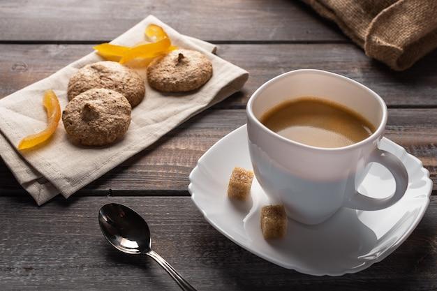 Чашка черного кофе с ложкой и комочки сахара рядом с ней - это печенье на льняной салфетке и