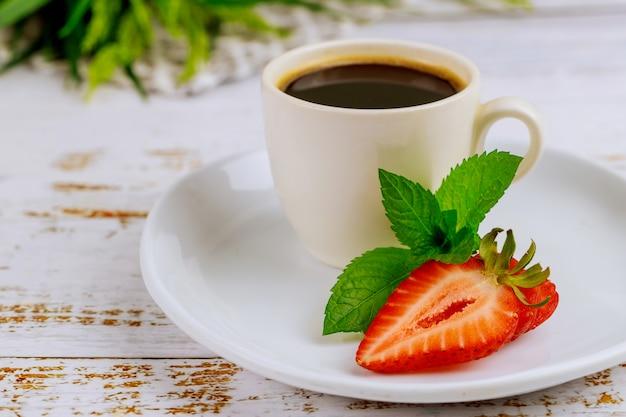 Чашка черного кофе с шоколадом и клубникой на белом столе