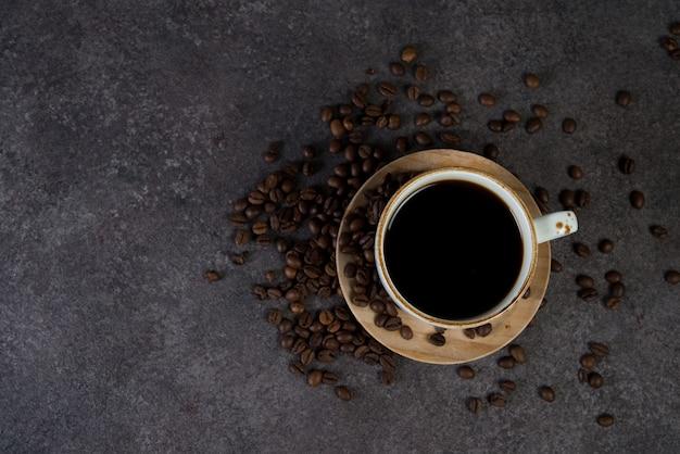 トップビューの周りのコーヒー豆とブラックコーヒーのカップ