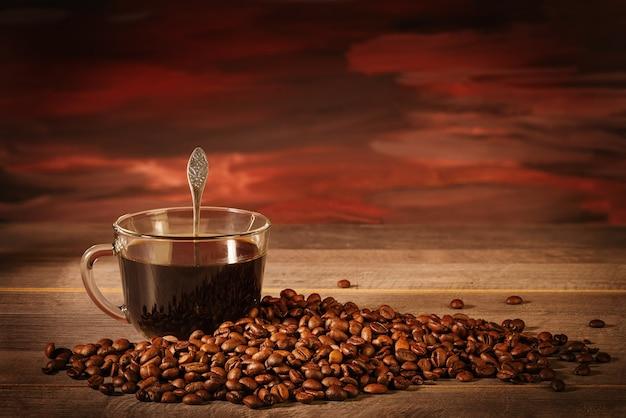テーブルの上のコーヒー豆とブラックコーヒーのカップ