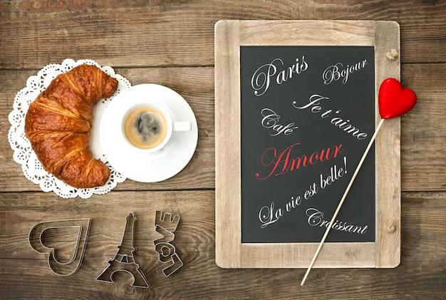 クロワッサン黒板とハートの装飾素朴な木製の背景とブラックコーヒーのカップ
